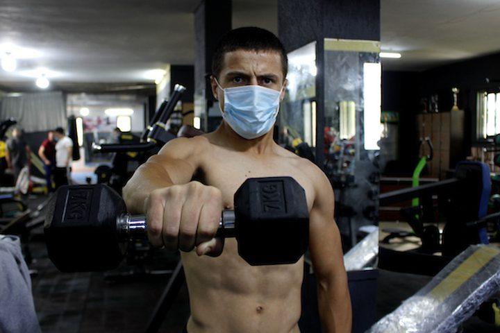 فلسطينيون يرتدون أقنعة كمال الأجسام كإجراء احترازي من انتشار فيروس كورونا (COVID-19) ، يتدربون خلال جلسة تمارين ، بعد قرار افتتاح الصالة الرياضية ، في مدينة الخليل بالضفة الغربية