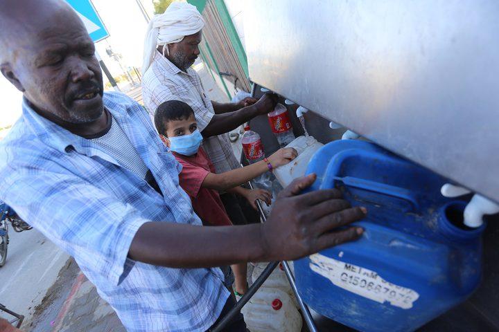 فلسطينيون يملأون الزجاجات من صنبور عام خلال فترة الاغلاق في غزة