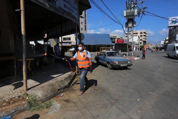 عمال فلسطينيون يعقمون الشوارع، خلال الإغلاق المفروض قطاع غزة