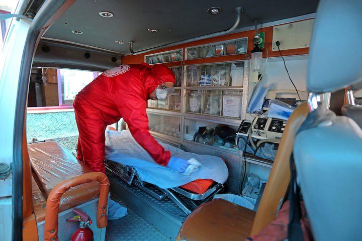 موظفون في الهلال الأحمر يرتدون ملابس واقية للعمل خلال فترة الاغلاق المفروضة في دير البلح لمنع تفشي فيروس كورونا
