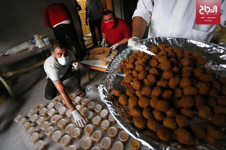 مواطنون يعدون الحمص والفلافل لتوزيعها على الأسر الفقيرة في دير البلح