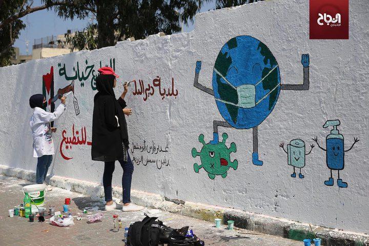 فنانون فلسطينيون يرسمون جدارية للتوعية من فيروس كورونا في دير البلح