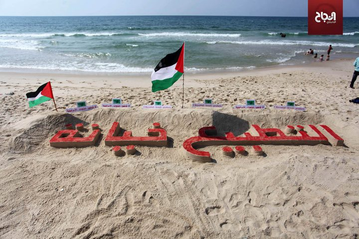 """فنان فلسطيني ينحت """"التطبيع خيانة"""" على رمال شاطىء غزة"""