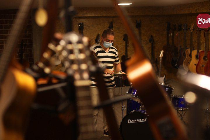 مواطنون يعرضون الآت موسيقية في متجرهم في مدينة غزة والذي أعيد فتحة جزئيًا بسبب أزمة كورونا