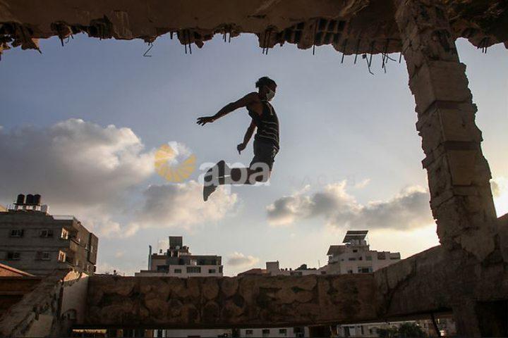 لاعبو باركور فلسطينيون يرتدون أقنعة ويظهرون مهاراتهم على سطح مبنى في مدينة غزة