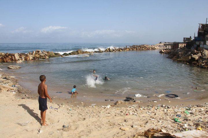 أطفال يسبحون على شاطىء البحر بمخيم الشاطئ غرب غزة