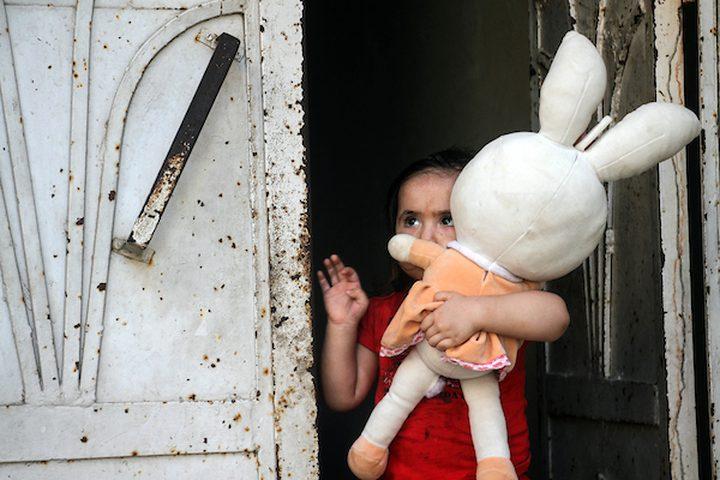 طفلة فلسطينية تحمل دميتها تقف على باب منزلها وسط تفشي مرض فيروس كورونا (COVID-19) في جباليا شمال قطاع غزة