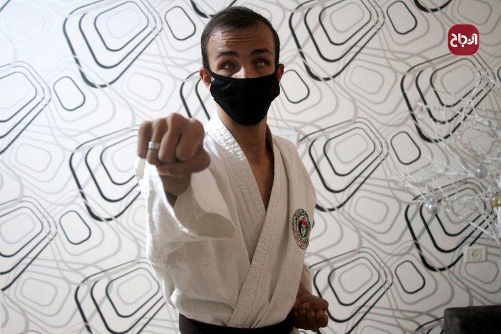 الكفيف مؤمن البيطار يدّرب الكاراتيه في منزله بعد قرار اغلاق الصالات الرياضية في غزة