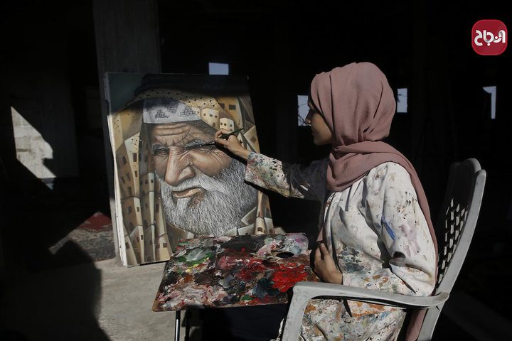 الفنانة الفلسطينية خلود الدسوقي تعلق لوحاتها في منزلها بخان يونس جنوب قطاع غزة