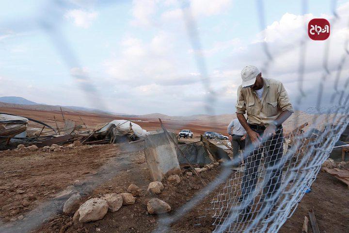مواطنون يقفون بجانب ممتلكاتهم بعد أن هدم الاحتلال خيامهم في تجمع حمصة-البقيعة شرق طوباس