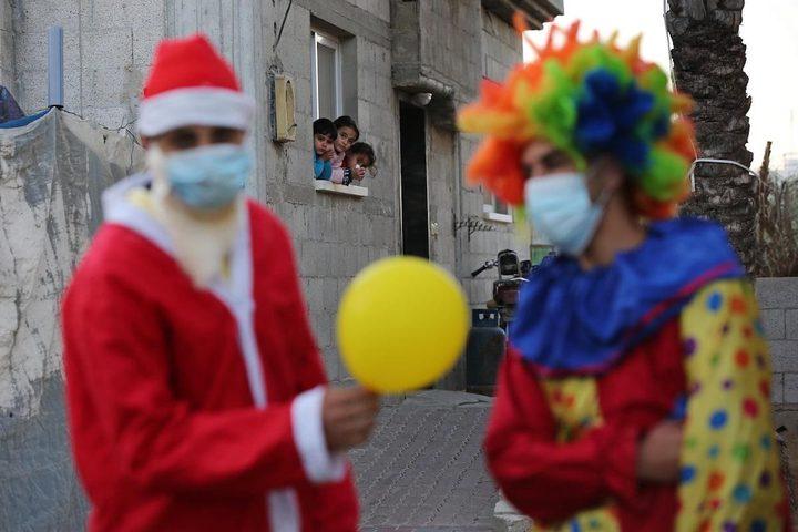 مواطنون يرتدون زي بابا نويل ويوزعون البالونات على الأطفال في خانيونس