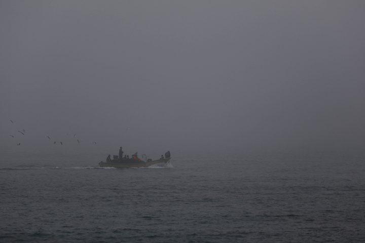 صيادون يعملون على قوارب الصيد الخاصة بهم خلال ضباب كثيف في غزة