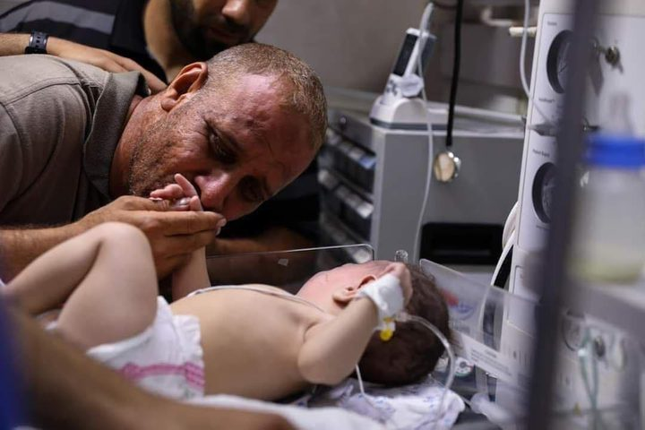 الفلسطيني محمد الحديدي يقبل يد طفله الناجي الوحيد من مجـزرة الشاطئ في غزة والتي راح ضحيتها 10 شهداء بينهم اطفال ونساء