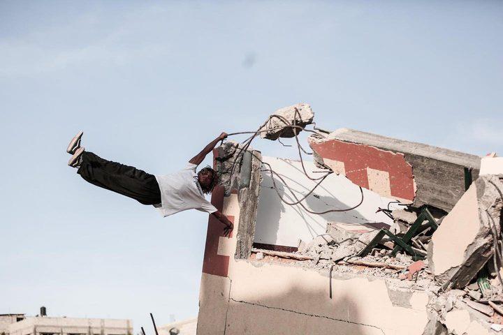 مجموعة من الشبان يمارسون رياضة الباركور على ركام المباني التي دمرها الاحتلال بقطاع غزة