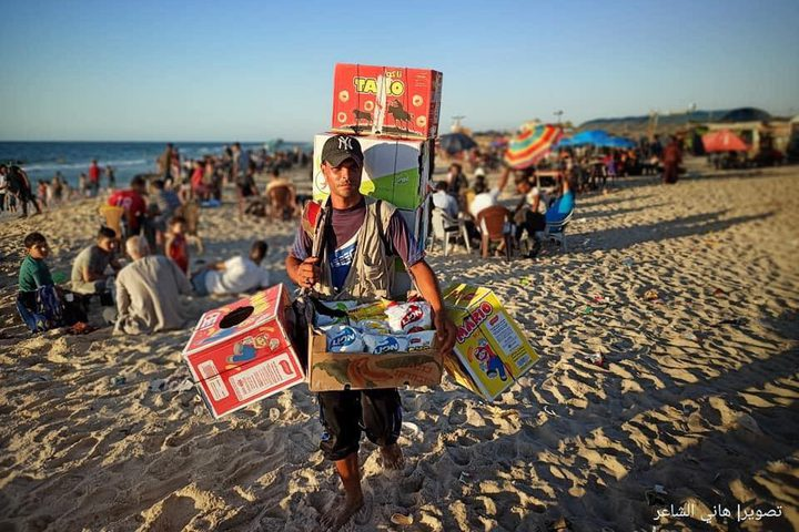 """شاب مكافح يحمل بقالة من """"الشبس"""" على ظهره لكسب لقمة العيش على شاطىء بحر محافظة خان يونس جنوبي قطاع غزة، تصوير هاني الشاعر"""