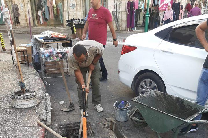 عمال قسم الصرف الصحي في بلدية نابلس يبدأون اليوم أعمال تنظيف مصارف الامطار في المركز التجاري وذلك تحسبا وتحضيرا لموسم الامطار والشتاء